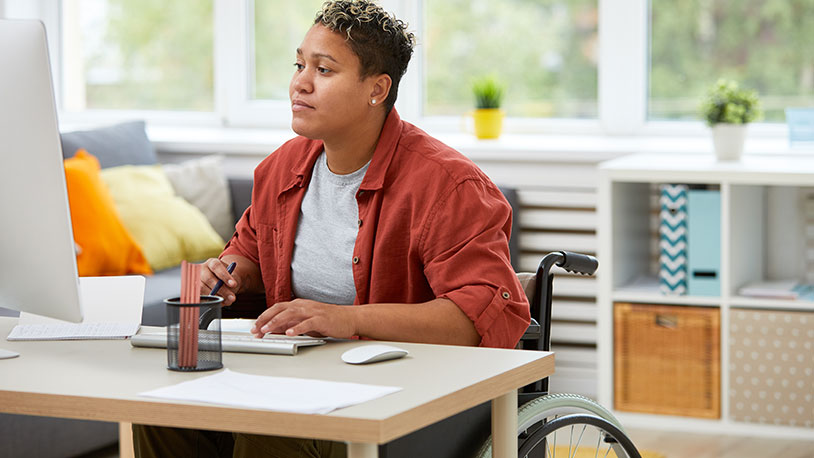 black woman in wheel chair working in office
